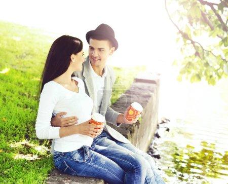 Photo pour Jeune couple heureux assis sur la bordure dans le parc. Amour, relation, sortir ensemble concept - image libre de droit