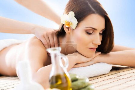 Photo for Young beautiful and natural woman on spa massage procedure over blue background. Spa, wellness and healthcare concept - Royalty Free Image