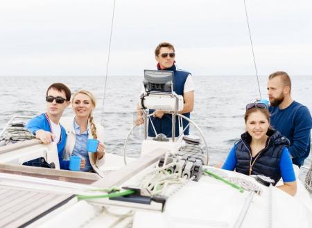 Group of happy friends having a party on a yacht