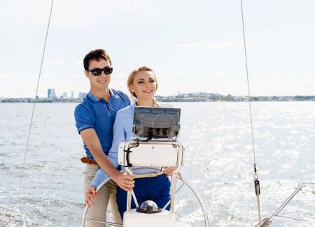 Happy and beautiful young couple relaxing on a yacht
