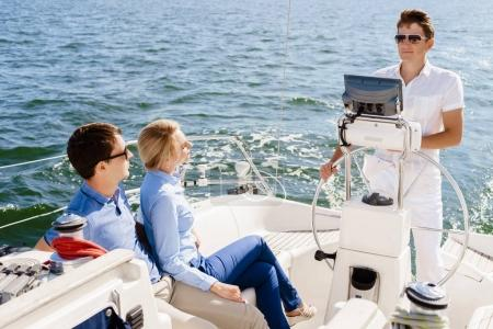 Happy and beautiful couple having a rest on yacht with a captain
