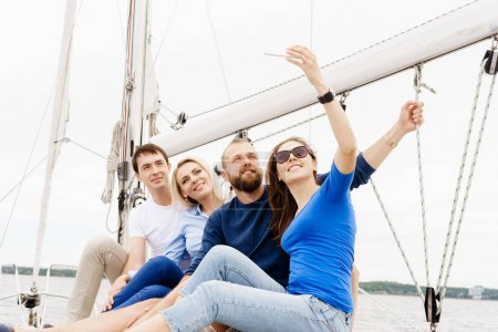 Group of happy friends traveling on a yacht and taking selfie