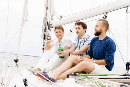 Happy friends sitting together on a deck of a yacht