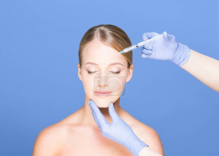 Doctor making injection into face of woman
