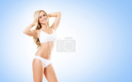 fit and sporty blonde woman in white lingerie over blue background. Sport, fitness, diet, weight loss and healthcare concept