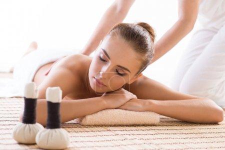 Photo pour Femme belle, jeune et saine dans le salon spa ayant massage. Massage, traitement, médecine traditionnelle et la notion de guérison - image libre de droit