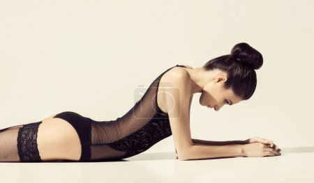 young and beautiful slim woman in black erotic bodysuit and stockings posing over white background