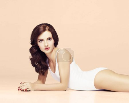fit and sporty woman in white lingerie bodysuit posing over pink background. Sport, fitness, diet, weight loss and healthcare concept