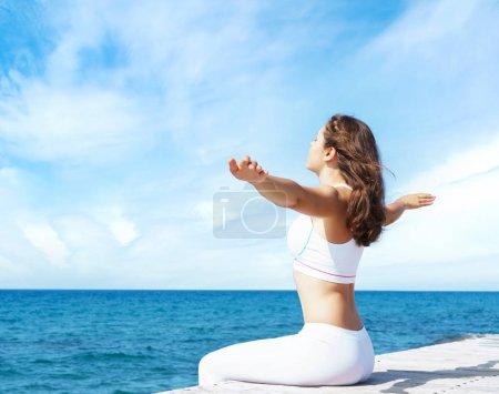 Photo pour Attrayant, belle et jeune fille en vêtements de sport blancs méditant sur une jetée en bois en été. Yoga, sport, loisirs, vacances et concept de voyage . - image libre de droit