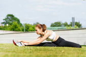 Young, fit and sporty girl stretching in the park. Fitness, sport, urban and healthy lifestyle concept.