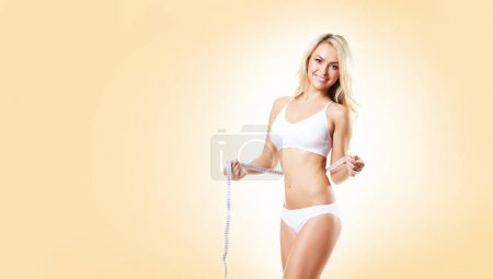 Photo for Fit and sporty girl in white underwear. Beautiful and healthy woman measuring her perfect body over yellow background. Sport, fitness, diet, weight loss and healthcare concept. - Royalty Free Image