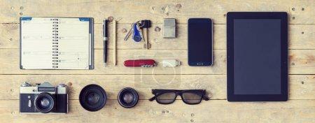Photo pour Tenue d'un voyageur élégant. Ensemble de différents objets et équipements : tablette, téléphone, album, lunettes, appareil photo, lentilles, gommes, couteau et montres - image libre de droit