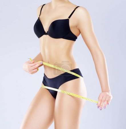 Fit, healthy and sporty female body isolated on white. Slender girl with measuring tape. Sport, fitness, diet, weight loss and health care concept.