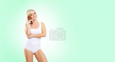Fit and sporty girl in white underwear. Beautiful and healthy woman posing over isolated green background. Sport, fitness, diet, weight loss and healthcare concept.