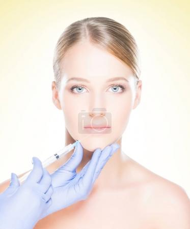 Young, beautiful and healthy woman having skin injections over yellow background. Plastic surgery concept.