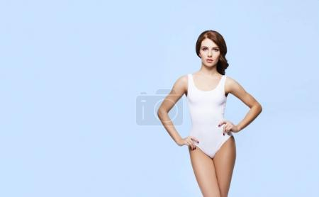 Photo for Fit and sporty girl in white underwear. Beautiful and healthy woman posing over cyan background. Sport, fitness, diet, weight loss and healthcare concept. - Royalty Free Image