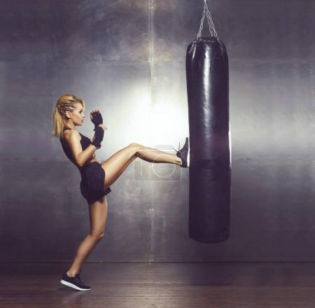 Fit and sporty young woman having a muay thai training. Girl training in undergorund gym. Health, sport, kickboxing, martial arts and fitness concept.