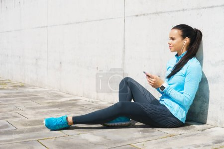 Young and fit woman listening to the music outdoor. Sport, fitness and healthy lifestyle concept.
