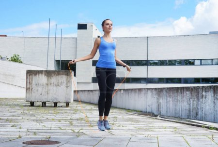 Young, fit and sporty girl jumping with a skipping rope. Fitness, sport, urban jogging and healthy lifestyle concept.