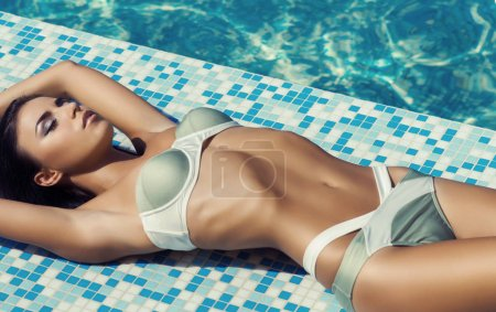 Sexy brunette woman in swimsuit relaxing in a tropical resort. Traveling and vacation concept.