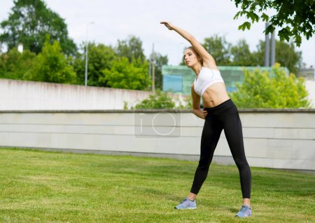 Young, fit and sporty girl stretching in the park. Fitness, sport, urban jogging and healthy lifestyle concept.