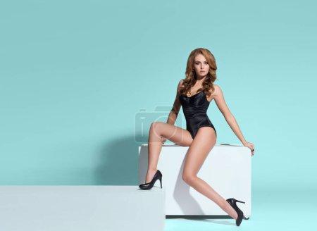 Photo pour Modèle de mode posant en sous-vêtements érotiques. Femme en belle lingerie noire sur fond coloré. - image libre de droit