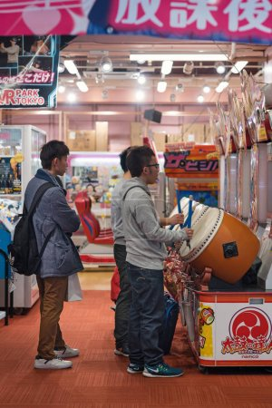 TOKYO, JAPAN - CIRCA MARCH, 2017: Young men having fun with drums inside a Pachinko.