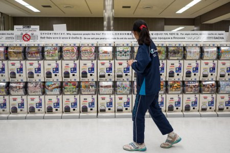 TOKYO, JAPAN - CIRCA MARCH, 2017: Woman in front of Japanese capsule toy vending machine Gachapon in Narita international airport. Gachapon is a Japanese vending machine dispensed capsule toy.
