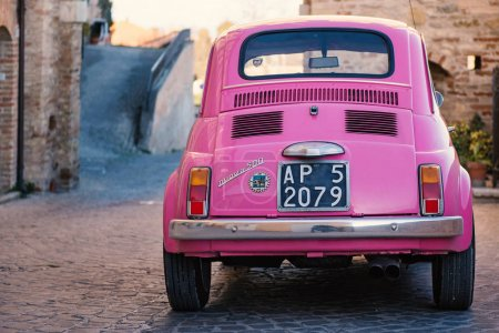 ALTIDONA, ITALY - FEBRUARY 20, 2016: Old pink Fiat Nuova 500 city car parked in a typical old village. Produced by the Italian manufacturer Fiat between 1957 and 1975.