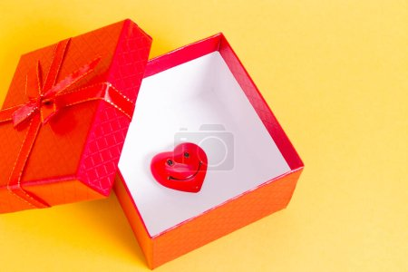 Red smiling heart in a red open box on a yellow ba...