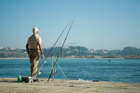 Senior man fishing on the coast of the ocean