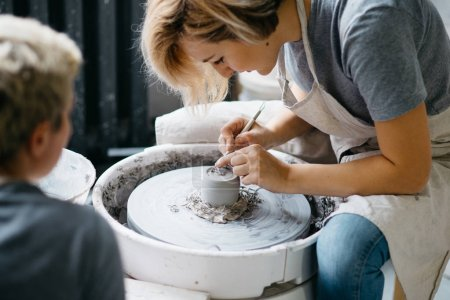 Potter working with clay on wheel
