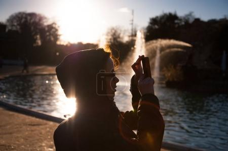 Travelling woman taking photo on cellphone