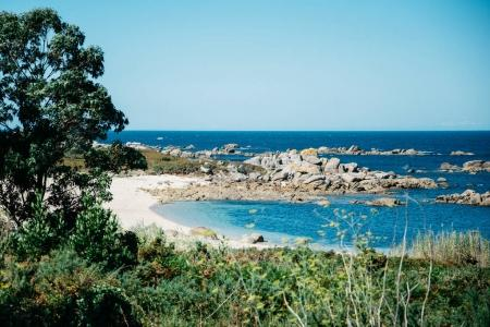 Rocky coastline landscape with white sand and blue sea water