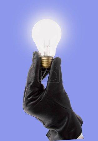 Photo pour Main avec des gants noirs tenant l'ampoule comme concept de la f d'idées sur fond bleu - image libre de droit