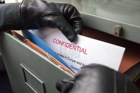 Photo pour Voleur volant des fichiers confidentiels dans un bureau - image libre de droit