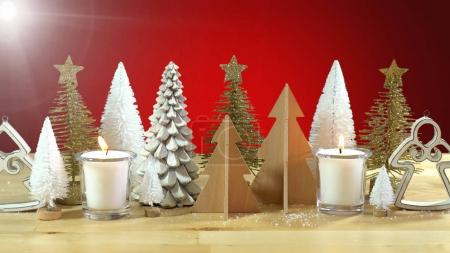 Photo for Christmas centerpiece or mantel decoration of rows of minature Christmas Trees with burning candles against a red background, with light flare. - Royalty Free Image