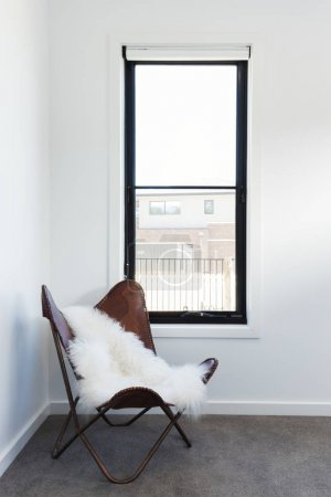Cute leather chair with sheepskin rug throw