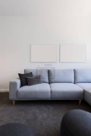 pastel blue sofa with blank artwork above