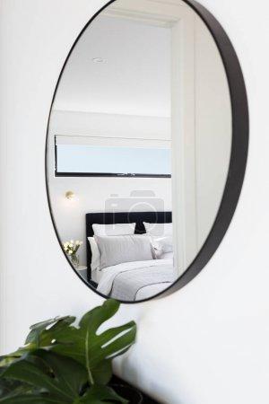 bedroom reflected in a hallway mirror