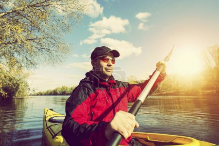 Photo for Man paddling in a kayak on river. - Royalty Free Image