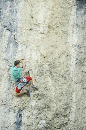 Photo pour Le grimpeur grimpe le rocher. - image libre de droit