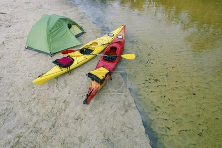 Rafting on kayaks. A tent camp stands on the river bank.