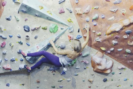 Photo for Young woman practicing rock-climbing on a rock wall indoors - Royalty Free Image