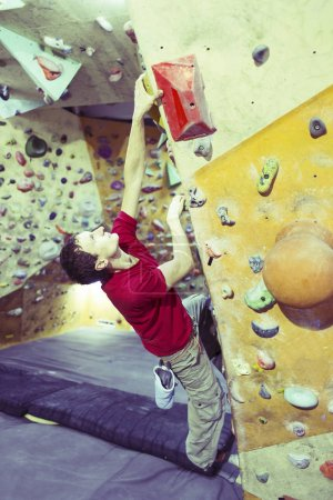 Photo for Young man practicing rock-climbing on a rock wall indoors. - Royalty Free Image
