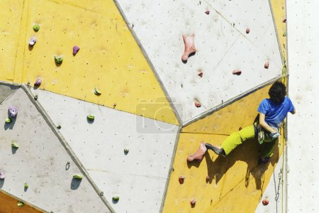 Photo for Fitness, extreme sport, bouldering, people and healthy lifestyle concept - young man exercising at indoor climbing gym - Royalty Free Image