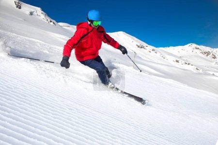 Man skiing on prepared slopes in Alps