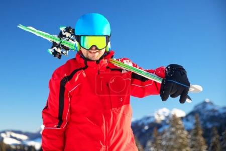 Young attractive caucasian skier with ski in Swiss Alps