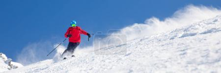 Man skiing on the prepared slope with fresh new po...