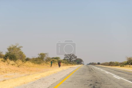 Poor people walking on the roadside in the rural Caprivi Strip, the most populated region in Namibia, Africa.